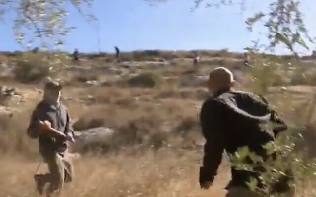 A settler with a cudgel (L) attacks Channel 12 news reporter Ohad Hemo during clashes with Palestinian olive harvesters in the West Bank village of Burka, October 13, 2020. (Screen capture: Twitter)