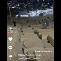 A video uploaded to TikTok shows two people running on graves at the Mount of Olives cemetery in Jerusalem. (Screen capture: Twitter)
