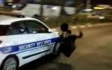 A security car drives away as a Haredi man protesting the extension of a lockdown over his city falls, in Beitar Illit on October 15, 2020. (Screen capture/Twitter)