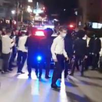 Ultra-Orthodox men block a police vehicle attempting to enforce coronavirus lockdown rules in Bnei Brak, October 4, 2020. (Screenshot: Twitter)