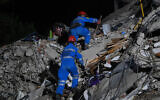 Rescuers search for survivors among the rubble of a collapsed building after a powerful earthquake struck Turkey's western coast and parts of Greece, in Izmir, in the early hours of October 31, 2020. (Ozan Kose/AFP)