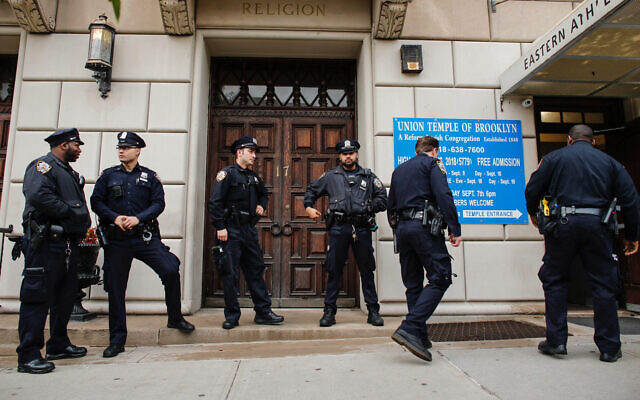Illustrative: New York police officers stand guard at the door of the Union Temple of Brooklyn, November 2, 2018. (Kena Betancur/AFP/Getty Images via JTA)