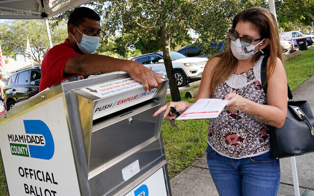 A voter drops off her ballot in North Miami, Florida, October 30, 2020. (AP Photo/Marta Lavandier)