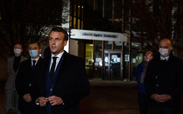 French President Emmanuel Macron speaks in front of a high school in Conflans Sainte-Honorine, northwest of Paris, after a history teacher who opened a discussion with students on caricatures of Islam's Prophet Muhammad was beheaded, October 16, 2020. (Abdulmonam Eassa, Pool via AP)