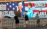 Backdropped by a billboard supporting US President Donald Trump and first lady Melania Trump, people wave flags on a bridge during a protest against Prime Minister Benjamin Netanyahu in Tel Aviv, October 3, 2020. (AP Photo/Oded Balilty)