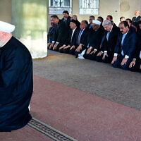 Syrian President Bashar Assad, right background, prays during Eid al Adha prayers behind Damascus Mufti Mohammed Adnan Afiouni, foreground, in Daraya town suburb of Damascus, Syria, in a photo released on September 12, 2016 by the Syrian official news agency SANA. (SANA via AP)