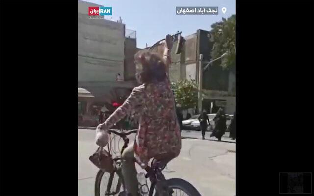 An Iranian woman illegally rides a bicycle without a hijab in the city of Najafabad. She was later arrested. (Screenshot/Twitter)