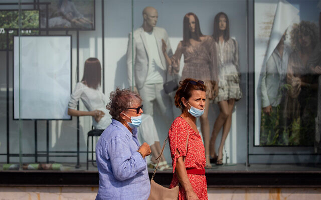 People walk past a closed shop at the Tel Aviv port, October 29, 2020. (Olivier Fitoussi/Flash90)