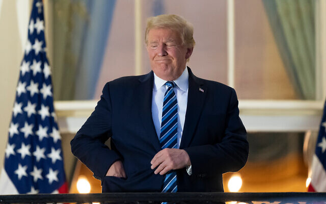 US President Donald Trump puts his mask in his pocket as he stands on the Blue Room Balcony upon returning to the White House from Walter Reed Medical Center, October 5, 2020. (AP Photo/Alex Brandon)