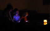 Illustrative: Israelis at home during a power outage in the coastal city of Netanyahu, October 26, 2015. (Chen Leopold/FLASH90)