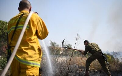 A firefighters and a soldier work together against a fire at the Kfar HaOranim settlemet in the West Bank, amid a rash of blazes throughout the country, October 9, 2020 (IDF)