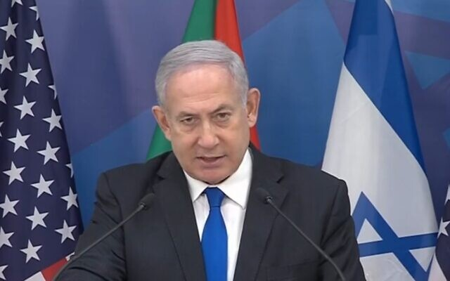 Prime Minister Benjamin Netanyahu discusses Israel's new accord with Sudan, with Israeli, Sudanese and American flags behind him, October 24, 2020 (video screenshot)