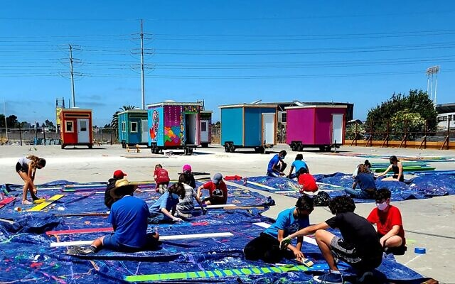 Campers from Camp Kee Tov, Congregation Beth El's Jewish summer camp, paint planks for the perimeter fence at the YSA Tiny House Village in Oakland, California on August 4, 2020. (courtesy Sally Hindman)