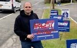 Congressional candidate Josh Eisen holds a campaign sign tagged with anti-Semitic graffiti. (Screenshot from News12 via JTA)