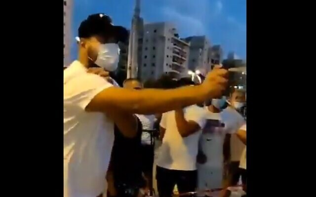 A right-wing protesters sprays mace at anti-Netanyahu demonstrators. October 13, 2020 (screen capture via Twitter)