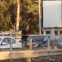 Dennis Potodinsky throwing rocks at anti-Netanyahu protestors. (Screengrab: Twitter)