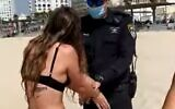 A woman is handcuffed on Tel Aviv beach after she refuses to identify herself to officers trying to issue a fine for not wearing a facemask, October 9, 2020 (Screen grab)