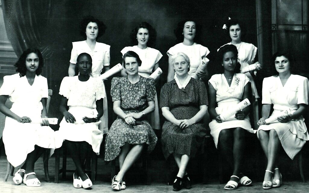 Jewish student Margo, top left, with her Greek, Armenian, Sudanese, and Egyptian classmates, and British faculty, in a 1948 graduation photo from the Unity High School she attended in Khartoum. All the girls are wearing pristine dresses and shoes in Western style. (Courtesy Tales of Jewish Khartoum)