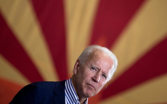 Joe Biden pauses while speaking to supporters in front of an Arizona state flag, at the United Brotherhood of Carpenters and Joiners of America's training center, on October 8, 2020, in Phoenix. (Brendan Smialowski/AFP)