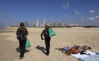 Israelis who lost their jobs due to Covid-19 coronavirus pandemic crisis, work on a new job collecting trash on the beach at the Peleg Nature reserve in the Mediterranean coastal city of Netanya on October 21, 2020. (Photo by MENAHEM KAHANA / AFP)