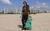 Israeli Lotem Benbenishti, 28, poses as she works on her new job collecting trash on the beach at the Peleg Nature reserve in the Mediterranean coastal city of Netanya on October 21, 2020. (Photo by MENAHEM KAHANA / AFP)