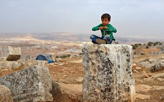 A Syrian child plays on November 1, 2020 at a makeshift camp of Syrians displaced by war at the UNESCO-listed site of Baqirha not far from the Turkish border, in a region of northwest Syria filled with abandoned Roman and Byzantine settlements (Abdulaziz Ketaz / AFP)