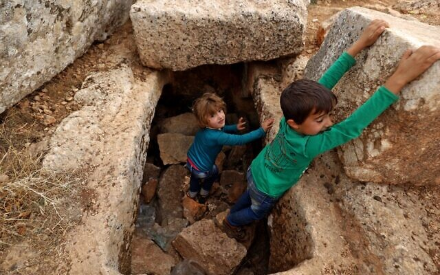 Syrian children play amid ruins on November 1, 2020 at the UNESCO-listed site of Baqirha not far from the Turkish border, in a region of northwest Syria filled with abandoned Roman and Byzantine settlements (Abdulaziz Ketaz / AFP)