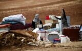 Illustrative: Palestinian bedouins stand next to their belongings after Israeli soldiers demolished their tents in an area east of the village of Tubas, in the West Bank, on November 3, 2020. (AAFAR ASHTIYEH / AFP)