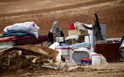 Palestinian bedouins stand next to their belongings after Israeli soldiers demolished their tents in an area east of the village of Tubas, in the West Bank, on November 3, 2020. (AAFAR ASHTIYEH / AFP)