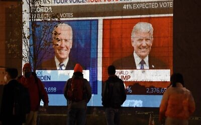 People watch a big screen displaying the live election results in Florida at Black Lives Matter plaza across from the White House on election day in Washington, DC, on November 3, 2020. (Olivier DOULIERY / AFP)