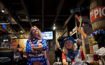 "People watch a broadcast of Fox News showing presidential election returns at an election night watch party organized by group ""Villagers for Trump"" in The Villages, Florida, on November 3, 2020. (Ricardo ARDUENGO / AFP)"