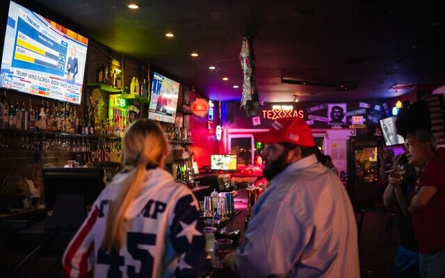 People watch as the election results come in at a pro US President Donald Trump watch party at the Rockin Cigar Bar, in defiance of a county wide shutdown order, in El Paso, Texas on November 3, 2020. (Justin HAMEL / AFP)