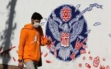 An Iranian man walks past a mural painted on the outer walls of the former US embassy in the Iranian capital Tehran, on November 4, 2020 as the US waits for the results of the presidential election. (ATTA KENARE / AFP)