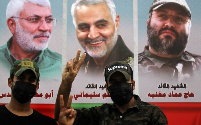 Supporters of the Iran-backed Popular Mobilization Forces paramilitary pose before a banner showing a montage of (L to R) slain Iraqi PMF commander Abu Mahdi al-Muhandis, Iranian Quds Force Gen. Qassem Soleimani and Lebanese Hezbollah military chief Imad Mughniyeh during a demonstration outside the entrance to the Iraqi capital Baghdad's highly-fortified Green Zone on November 7, 2020, demanding the departure of remaining US forces from Iraq. (Ahmad Al-Rubaye/AFP)