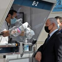 Mask-clad Prime Minister Benjamin Netanyahu is shown a demonstration of a coronavirus swab sampling during the inauguration of a COVID-19 coronavirus rapid testing center at Ben Gurion International Airport in Lod on November 9, 2020. (ATEF SAFADI / POOL / AFP)