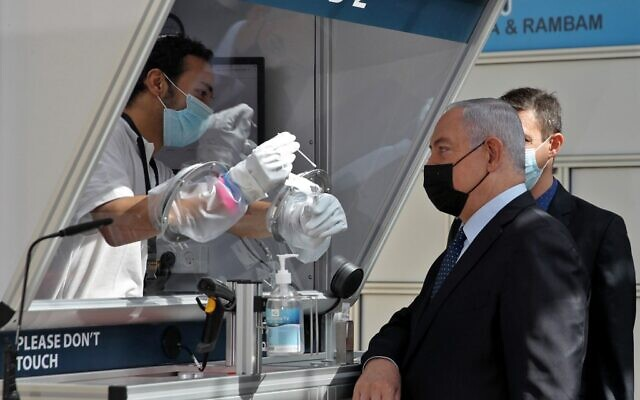 Mask-clad Prime Minister Benjamin Netanyahu is shown a demonstration of a coronavirus swab sampling during the inauguration of a COVID-19 coronavirus rapid testing center at Ben Gurion International Airport in Lod on November 9, 2020. (ATEF SAFADI / POOL / AFP)
