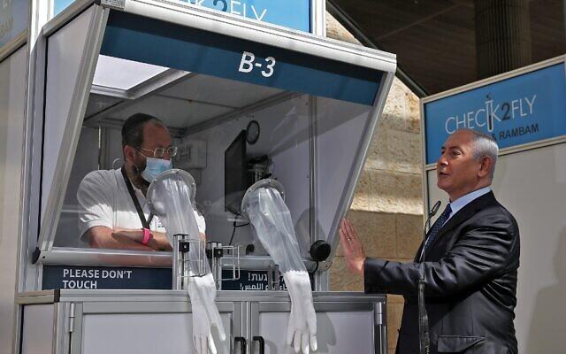 Mask-clad Prime Minister Benjamin Netanyahu speaks with a coronavirus swab sampling booth technician during the inauguration of a COVID-19 coronavirus rapid testing center at Ben Gurion International Airport in Lod on November 9, 2020. (ATEF SAFADI / POOL / AFP)