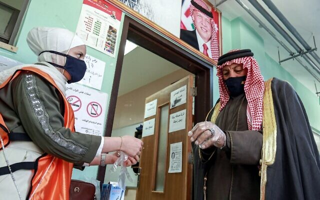 A voter is assisted by a volunteer to put on a plastic glove before entering a polling station in Jordan's capital Amman on November 10, 2020. (Khalil MAZRAAWI / AFP)