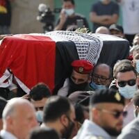 Palestinian mourners and an honor guard carry the coffin of late Palestinian negotiator Saeb Erekat during his funeral procession in the West Bank city of Jericho on November 11, 2020 (Ahmad GHARABLI / PPO / AFP)