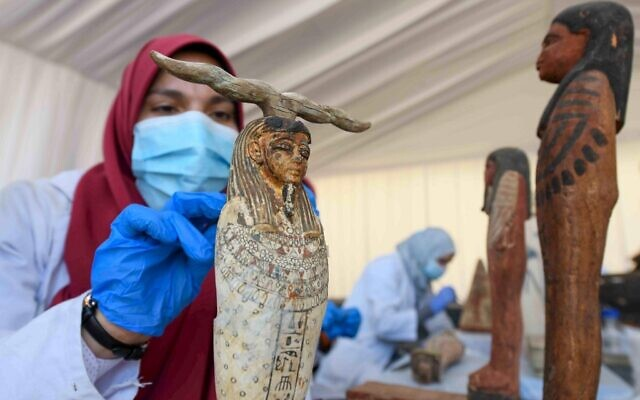 An archaeologist cleans a statue during the unveiling of an ancient treasure trove of more than a 100 intact sarcophagi, at the Saqqara necropolis 30 kms south of the Egyptian capital Cairo, on November 14, 2020 (Ahmed HASAN / AFP)