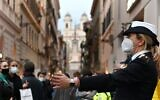 A municipal police officer wearing a face mask controls pedestrian traffic on Via dei Condotti shopping street in downtown Rome on November 14, 2020, during the Covid-19 pandemic caused by the novel coronavirus. (Alberto PIZZOLI / AFP)
