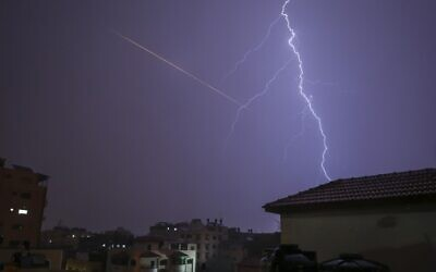 This picture taken from Gaza City shows lightning flashing over buildings as the flare of a rocket launch is seen nearby during a thunderstorm in Gaza city on November 15, 2020. (MOHAMMED ABED / AFP)