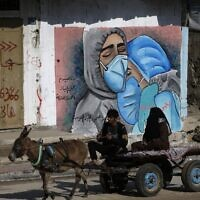 A Palestinian man and his wife ride a donkey cart past street art showing doctors mask-clad due to the COVID-19 pandemic in the Nusseirat refugee camp in the central Gaza Strip on November 16, 2020. (MOHAMMED ABED / AFP)