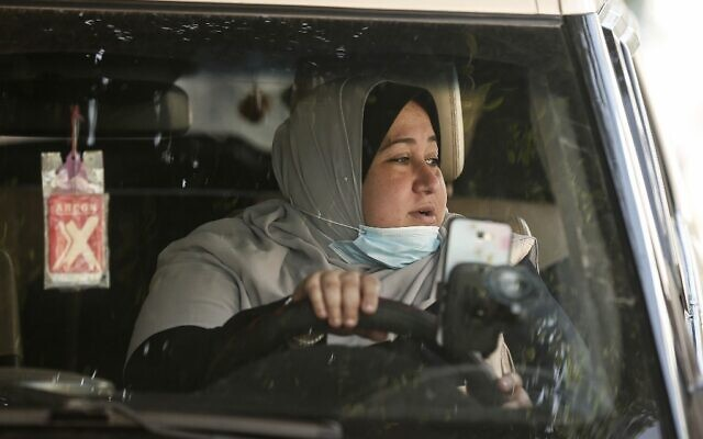 The first female Palestinian taxi driver in the Gaza Strip, Nayla Abu Jubbah, sits at her vehicle as she works in Gaza City on November 17, 2020. (Mahmud Hams/AFP)