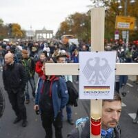 "A demonstrator carries a cross with the inscription ""German Constitution Law"" during a protest against measures imposed by the German government to limit the spread of the coronavirus, on November 18, 2020 near the Brandenburg Gate in Berlin. (Photo by Odd ANDERSEN / AFP)"