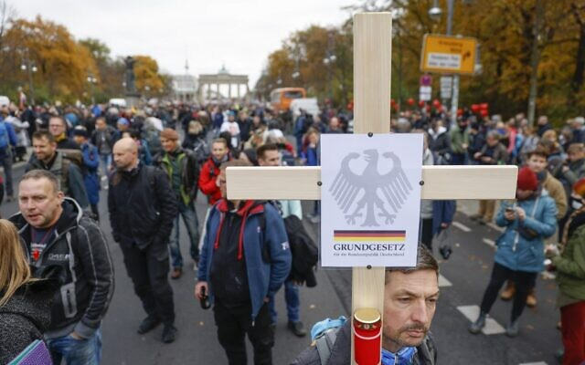 """A demonstrator carries a cross with the inscription """"German Constitution Law"""" during a protest against measures imposed by the German government to limit the spread of the coronavirus, on November 18, 2020 near the Brandenburg Gate in Berlin. (Odd ANDERSEN / AFP)"""