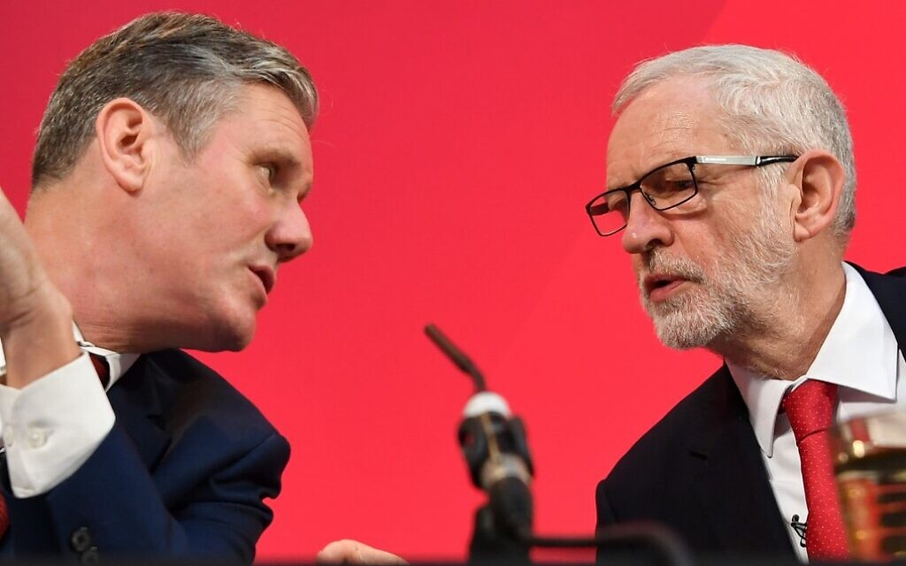 In this file photo from December 6, 2019 former opposition Labour party leader Jeremy Corbyn (R) speaks with his former Brexit secretary Keir Starmer during a press conference in London. (Ben Stansall/AFP)