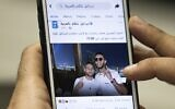 A man in Cairo holds a phone showing a picture of Egyptian singer Mohamed Ramadan posted by the official Facebook page of the State of Israel in Arabic showing Ramadan, right, hugging Israeli soccer player Diaa Sabia in Dubai, November 22, 2020. (Khaled Desouki/AFP)