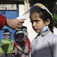 Palestinian children have their temperature checked as they arrive at a kindergarten in Gaza city while wearing face shields due to the COVID-19 pandemic, on November 23, 2020. (MOHAMMED ABED / AFP)