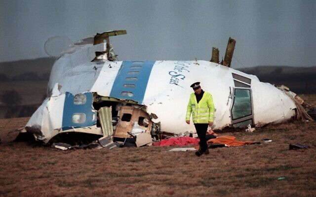 A policeman walking away from the damaged cockpit of the 747 Pan Am airliner that exploded and crashed over Lockerbie, Scotland, with 259 passengers on board, December 22, 1988. (ROY LETKEY/AFP)